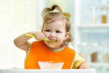 bigstock-Smiling-Kid-Eating-Food-On-Kit-72350332
