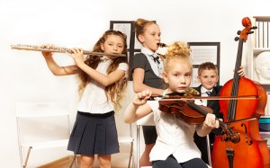 School children playing musical instruments together during their concert in school