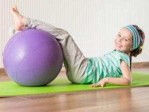 18568953 - smiling girl with the fitness ball at home